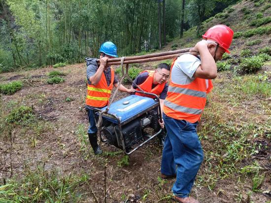 图为工作人员雨中搬运发电机。