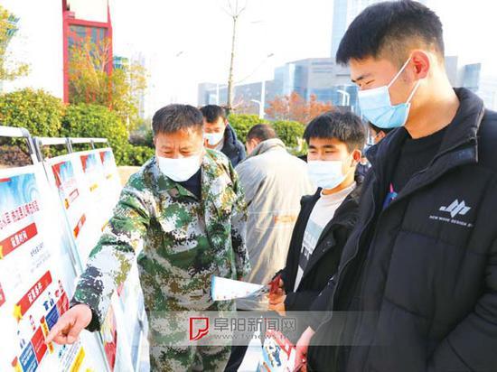 征兵宣传活动现场,适龄青年正在咨询了解相关征兵政策。