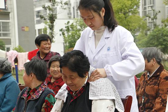 安徽中医药大学志愿者高宇为老奶奶进行推拿服务