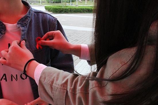 志愿者为参与者佩戴红丝带