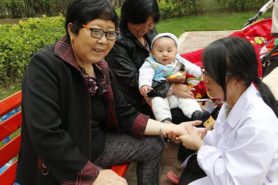 安徽中医药大学志愿者辛伟为李妈妈按摩腕部