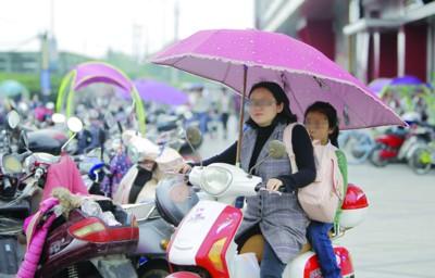 市民骑行装有遮雨棚的电瓶车