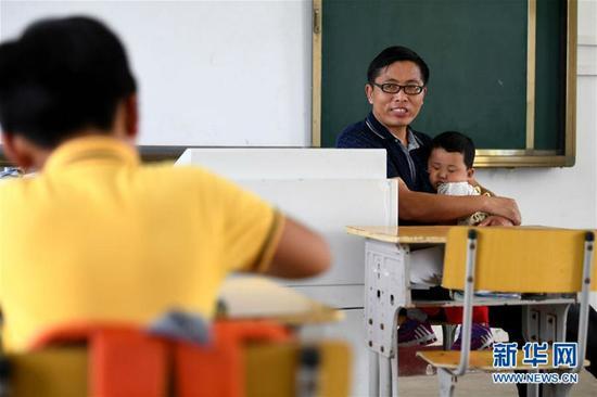 9月5日,汪开宽抱着3岁多的唐文先看孩子们写字。