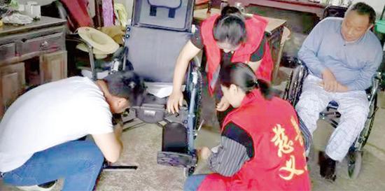 志愿者在残疾人家中组装轮椅。