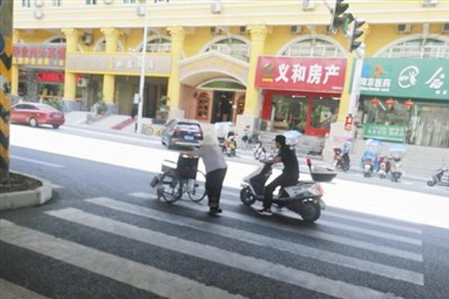 """老人推轮椅过马路 95后城管巡查员""""拦车""""护送"""