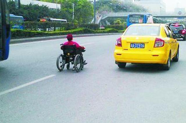 """老人""""驾""""着电动轮椅穿行在车流中"""
