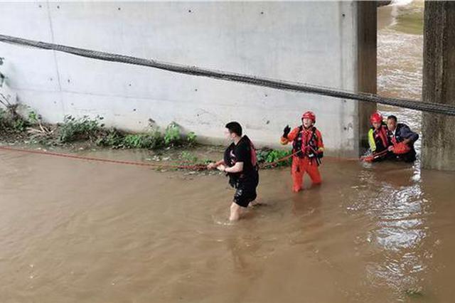 安徽一车辆被洪水围困 救援人员绳索相连救出被困人员