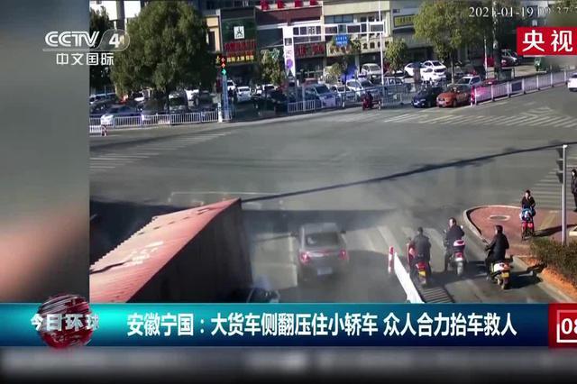 宁国:大货车侧翻压住小轿车 众人合力抬车救人