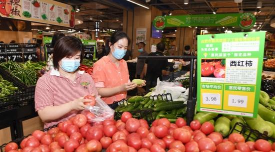 市民正在包河区世纪社区一家大型超市里选购物蔬菜