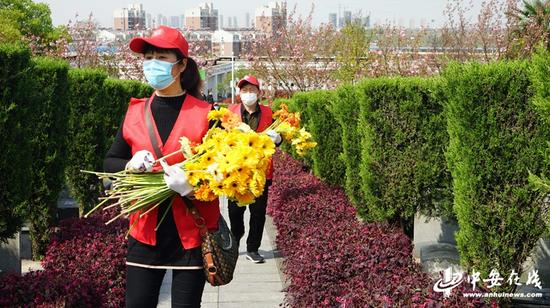 志愿者手捧鲜花,神情庄重