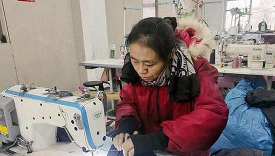 望江县鸦滩镇麦元村扶贫车间里工人在加工童装。 全媒体记者 付玉 摄