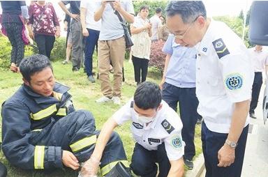 ↑救护人员正在为一位消防人员的脚部伤势进行处理。