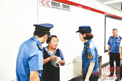 执法人员劝离乞讨人员。
