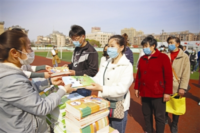3月24日,全椒县江海小学学生家长在学校排队领取消毒处理后的新教材。特约摄影禹强云摄
