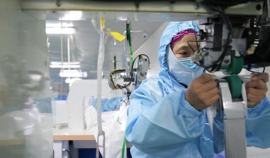 应急药品生产企业,一名工人正在专注地操纵机器