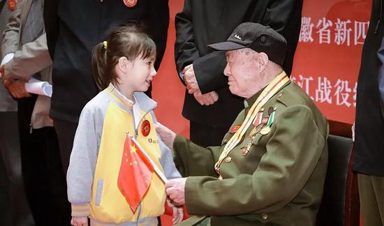 活动现场,一名小女孩向新四军老战士孔令科献国旗。