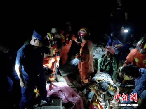 宜宾消防救援支队指战员搜救被埋压的群众。文/中新社记者 刘忠俊 四川消防供图