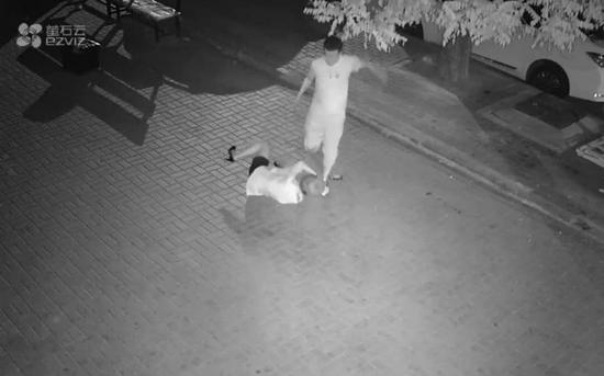 男子当街殴打女孩。监控视频截图