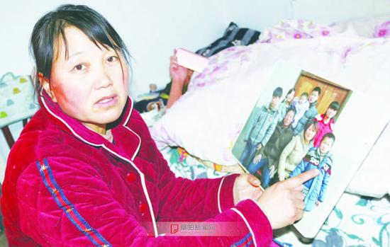 小豪的妈妈看着生病前儿子的照片,期盼儿子早日恢复健康