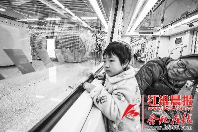一位参加试乘体验的小朋友好奇地看着车站。