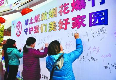 社区居民在禁燃禁放宣传板上签上自己的名字。 杨兵 图