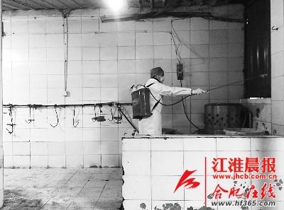 工作人员正对活禽市场进行消毒。