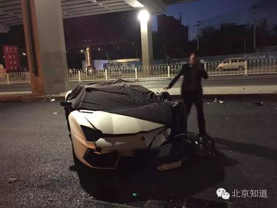 一男子用黑色车罩套住了车头及车顶。