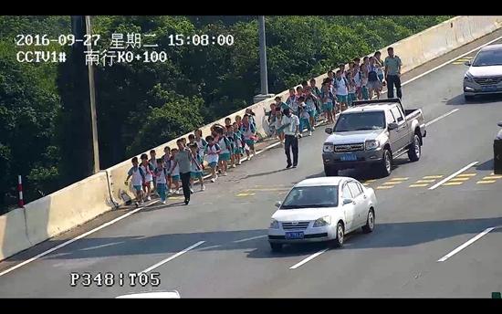3名官兵将车内小学生一个个抱下。