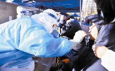 采样点的医务人员仔细为每一位市民进行检测