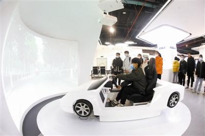 """图为虚拟驾驶VR体验项目,让体验者佩戴VR眼镜,坐在模拟驾驶舱,""""开车""""游览感受校园美景。"""