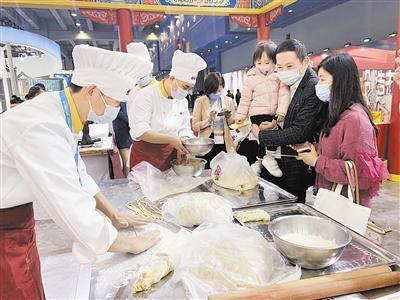 在天津展示交流区,桂发祥十八街麻花食品公司工作人员正在展示手工搓制工序。