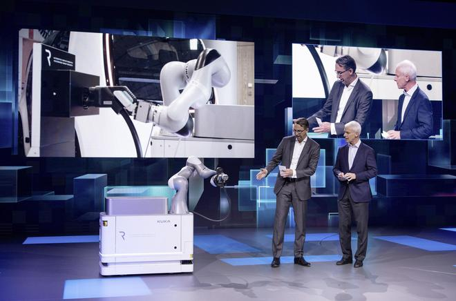 """大众汽车集团CEO穆伦(图右)与库卡(Kuka)公司CEO Till Reuter(图左)共同展示了首款可移动的电动汽车充电机器人""""CarLa"""""""