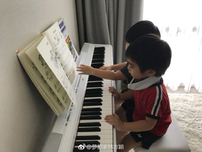 们坐在一起翻阅钢琴谱子,气氛融洽.-林志颖晒双胞胎儿子四手联