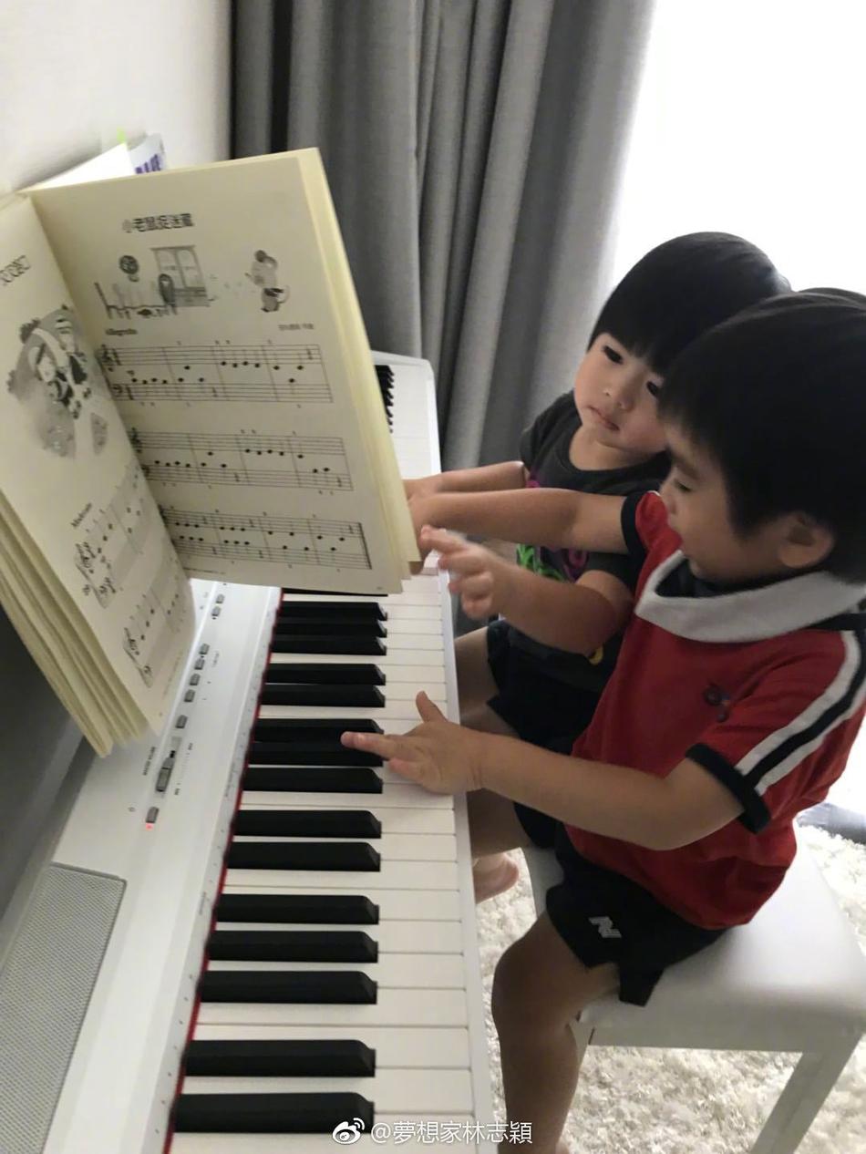 们坐在一起翻阅钢琴谱子,气氛融洽.-林志颖晒双胞胎儿子四手联弹