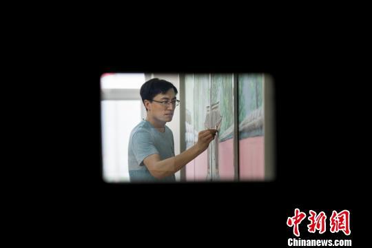 """""""80后""""美术教师赵文瑞正在黑板上完善他创作的一幅名为""""红墙绿荫""""的粉笔画。 韦亮 摄"""