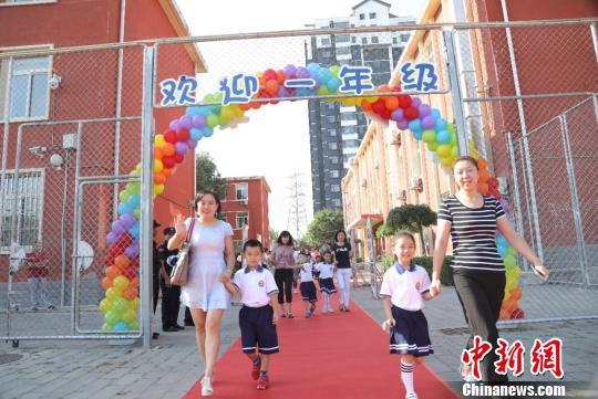 """一年级的新同学们在家长们的带领下跨过一道""""彩虹门""""。 学校供图 摄"""