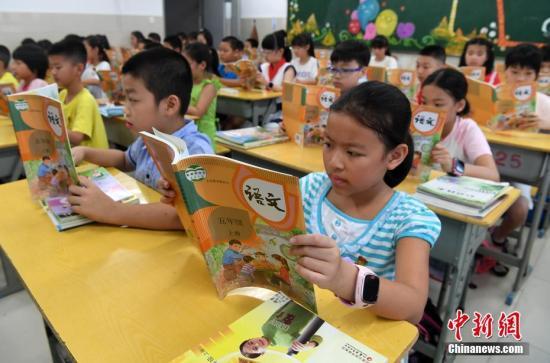 资料图:2019年9月1日,福州中山小学五年级学生在阅读统一部编版的语文教材。张斌 摄