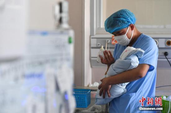 资料图:医生给婴儿喂奶。中新社记者 任东 摄