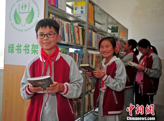 """资料图:小学生在""""绿书""""书架上挑选自己喜爱的课外书 史伟 摄"""