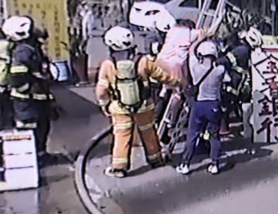 消防员引导老人下楼(图源:台媒)