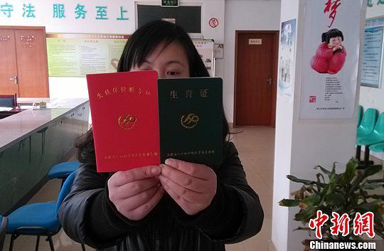 资料图:计生工作人员展示二孩生育证。中新社发 韩苏原 摄