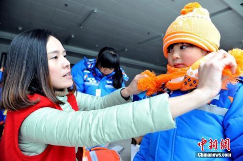 资料图:志愿者为贫困学生系上围巾。 邓龙华 摄