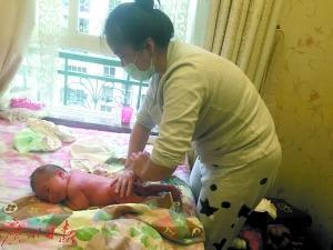 月嫂张英在给宝宝按摩。