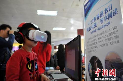 """资料图:一名 8岁小男孩正在体验""""VR阅读""""。 刘占昆 摄"""
