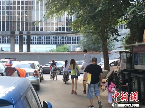 资料图:北京某幼儿园门口,家长接孩子放学。汤琪 摄