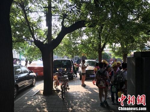 资料图:北京某小学门口等待家长接送的学生。汤琪 摄