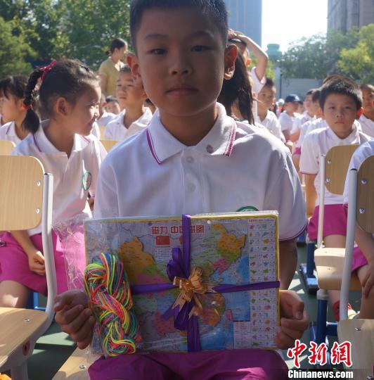 """学生赠送""""中国地图""""和""""彩色翻绳""""。 杜燕 摄"""