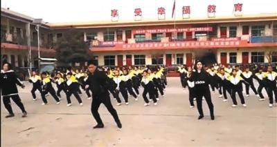 网络视频显示,校长张鹏飞在学校操场带领学生跳舞。视频截图