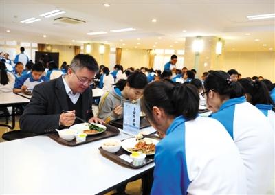 3月25日,海淀教师进修学校附属实验学校(北校区)食堂内,校长董红军与同学们一起就餐。新京报记者 王远征 摄