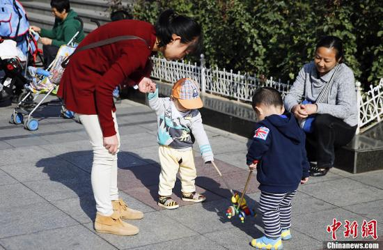 资料图:北京街头两名孩子在母亲的带领下玩耍。中新社发 张浩 摄